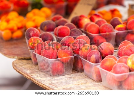 Ripe fresh peaches in a farmers market. Horizontal shot with a selective focus - stock photo