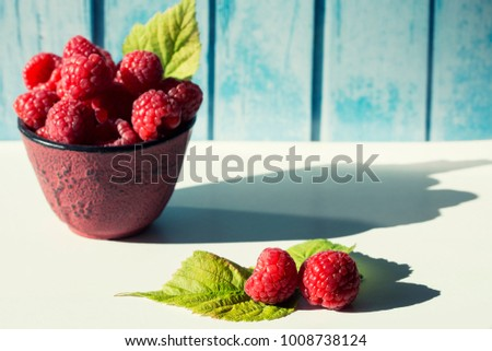 ripe fresh raspberries with leaves on a blue wooden background
