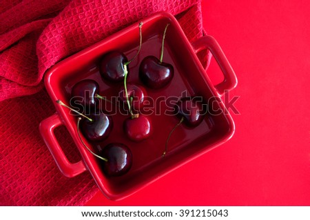 Ripe fresh shiny and juicy cherries in a red square bowl on a table with red kitchen towel. Top view, copy space, different shades of red.