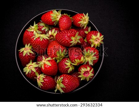Ripe fresh strawberry in bowl on black background, top view - stock photo