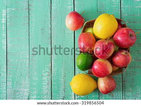 Ripe fruits (apples, lemons and limes) on a bright wooden background. Top view - stock photo