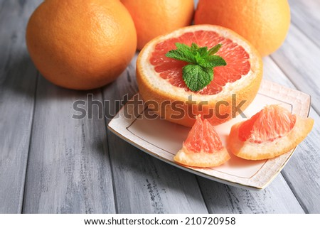 Ripe grapefruits on plate on color wooden background - stock photo