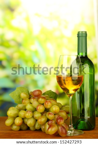 Ripe grapes, bottle and glass of wine, on bright background