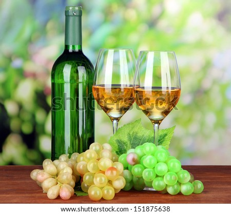 Ripe grapes, bottle and glasses of wine, on bright background