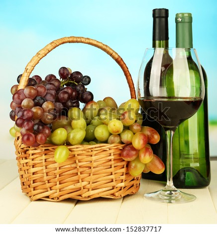 Ripe grapes in wicker basket, bottles and glass of wine, on bright background
