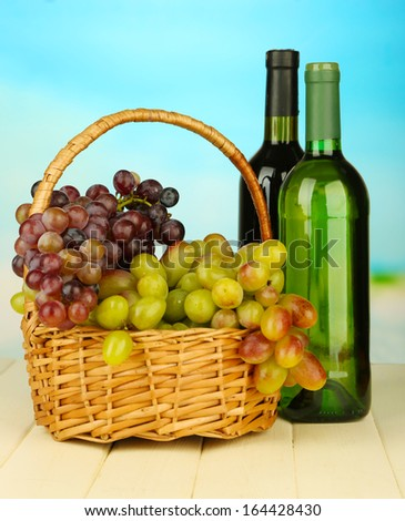 Ripe grapes in wicker basket, wine bottles, on bright background