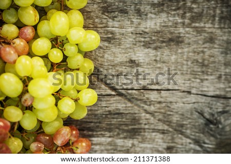 Ripe grapes on a wooden table outdoors. Fresh rich grapes on the vintage wooden table in the vineyard. Good harvest concept.