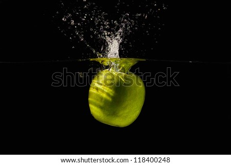Ripe green apple falling into the water with a splash on a black background closeup - stock photo