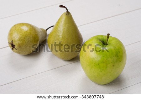 Ripe green apple with pears on a white wooden surface closeup. Top view - stock photo