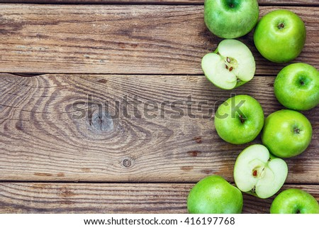 Ripe green apples and apple slices on old wooden background. Place for text. Top view - stock photo