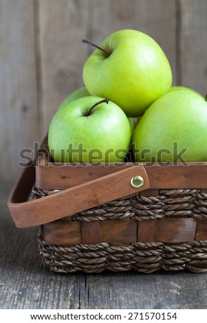 Ripe green apples (Golden Delicious) in a basket on the wooden table, selective focus - stock photo