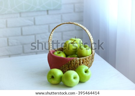 Ripe green apples in basket on a kitchen table - stock photo