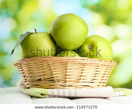 Ripe green apples with leaves in basket, on wooden table, on window background