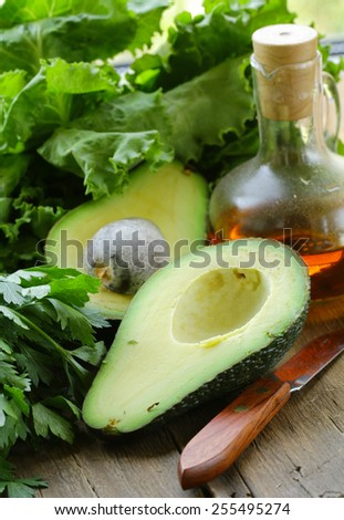ripe green avocado cut in half on a wooden table - stock photo