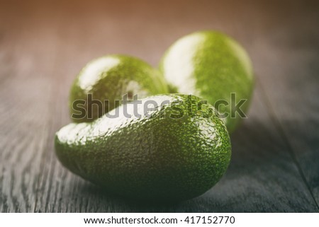 ripe green avocados on wood table, vintage toned - stock photo