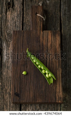 Ripe green peas and pods on a wooden background - stock photo