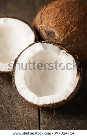Ripe half cut coconut on a wooden background. Ripe half cut coconut with milk on a wooden background - stock photo