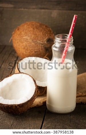 Ripe half cut coconut with milk on a wooden background.  - stock photo