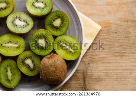 Ripe half kiwi fruits against a rustic wooden background. Healthy eating. - stock photo
