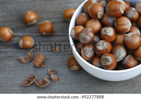 ripe hazelnuts in a bowl on a wooden table