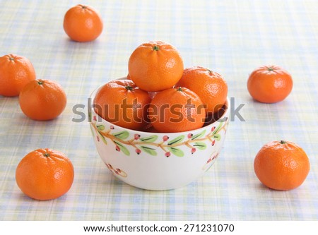 Ripe, juicy and delicious mandarin oranges are placed in a bowl. Bowl is placed on a table  with early morning sunlight falling on the fruits.  Concept image for healthy eating. - stock photo