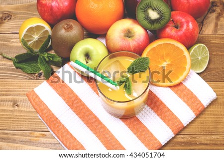 Ripe juicy delicious oranges, apples, lime and kiwi close with a glass of refreshing orange juice with mint and ice on a towel on the wooden table. Fruit juice in glass with straws. - stock photo