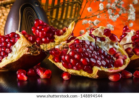 Ripe juicy fruit of the broken pomegranate on a colored background - stock photo