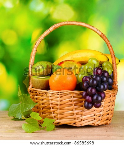 Ripe juicy fruits in basket on wooden table on green background - stock photo