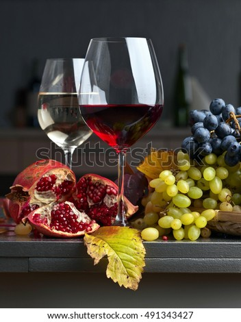 Ripe juicy grape and glass of wine on a kitchen table