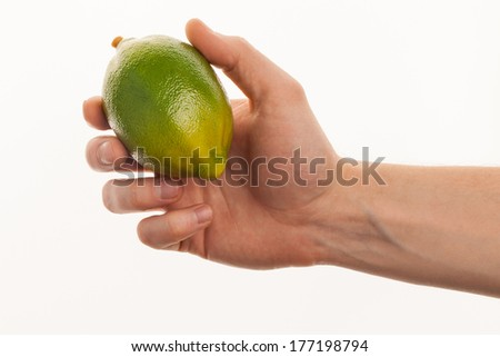 Ripe juicy lime in hand. Isolated on a white background. - stock photo