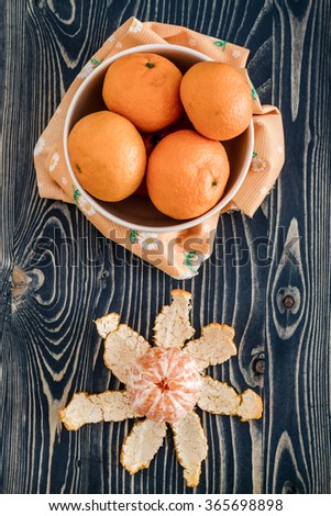 Ripe juicy mandarin fruits in white bowl on blue wooden background - stock photo