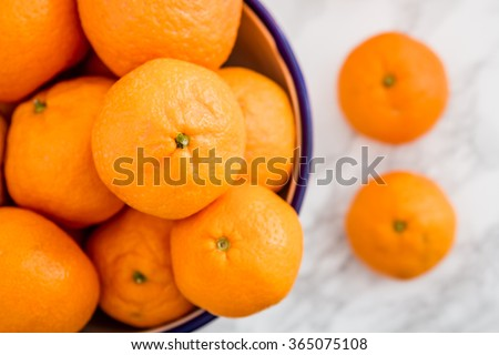Ripe juicy mandarin tangerine citrus fruit in enamel bowl on white marble