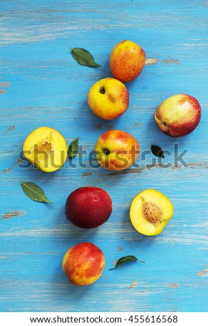 Ripe juicy nectarines over blue wooden table. Top view. Space for text - stock photo