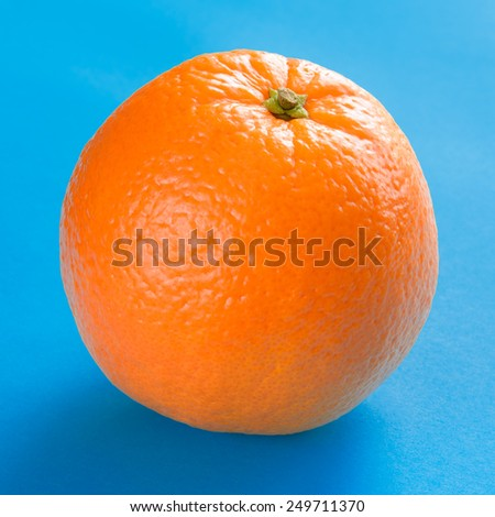 Ripe Juicy Orange Isolated on the Blue Background - stock photo