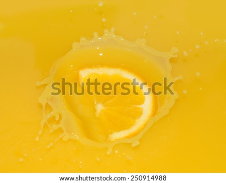 Ripe Juicy Orange Slice Falling into Juice - stock photo