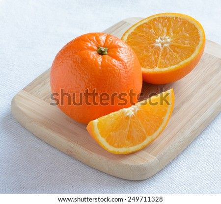 Ripe Juicy Orange with Slices on the Wooden Board - stock photo