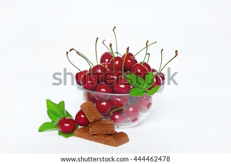 Ripe juicy red cherry with mint and chocolate in glass bowl on white background closeup. The natural background. - stock photo