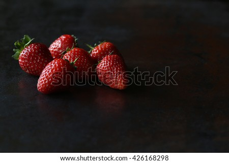 Ripe  juicy strawberries on the black table. Red fresh strawberries background. Rich summer strawberry crops, organic farming - stock photo