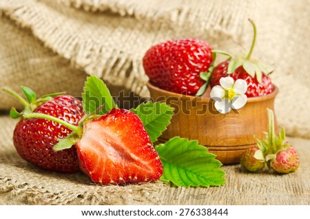 Ripe juicy strawberries on wooden table with burlap