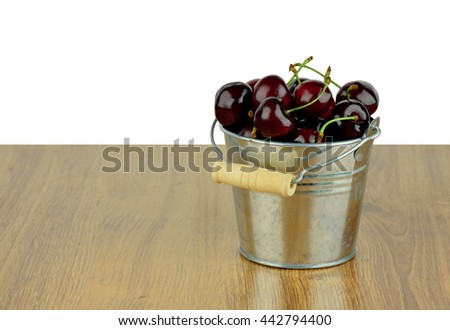 Ripe juicy sweet cherries in a small metal bucket on wooden background. Season goodies. Snack. Diet. Natural vitamins./ Isolated on white / - stock photo