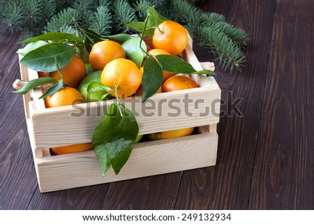 Ripe juicy tangerine, orange mandarin with leaves on wooden table - stock photo