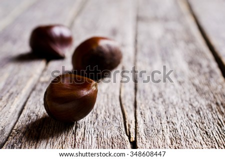 Ripe large chestnuts on a wooden surface. Selective focus.