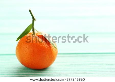 Ripe mandarin on a mint wooden table - stock photo