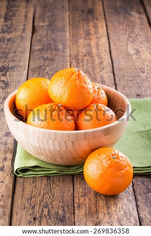 Ripe mandarins in a bowl on a wooden table - stock photo