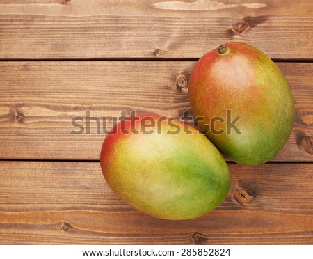 Ripe mango fruit lying over the brown colored wooden board surface as a background composition - stock photo