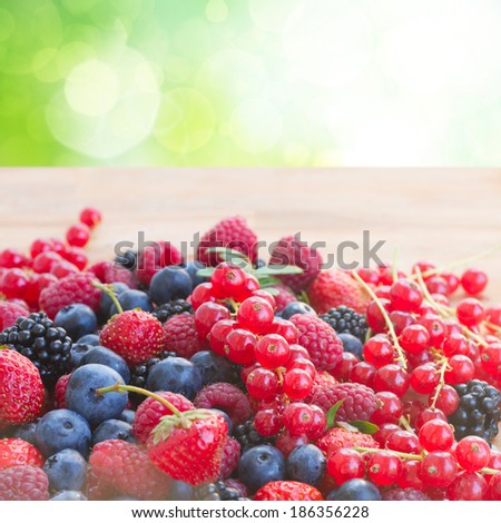 ripe of berries on wooden table  - blackberry, raspberry , red currant and blueberry
