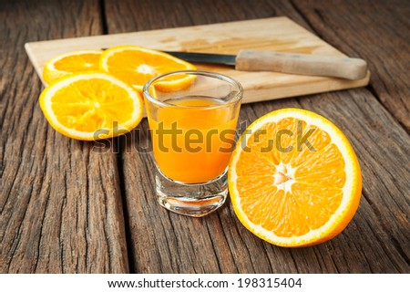 Ripe orange and orange juice on wooden table - stock photo