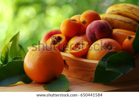 ripe orange and various fruits on wooden basket