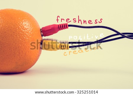 Ripe orange connected with three colored cables. - stock photo