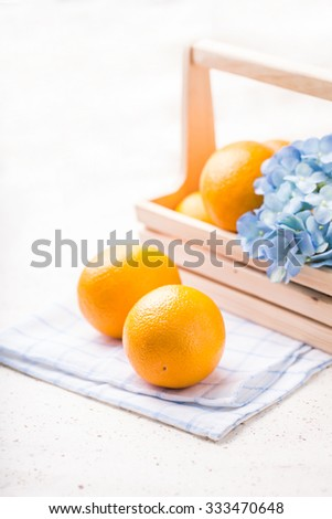 Ripe oranges and Hydrangea in wooden basket